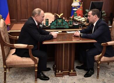 Russian President Vladimir Putin speaks with Russian Prime Minister Dmitry Medvedev.