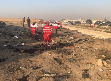 Workers near debris from the plane crash on the outskirts of Tehran