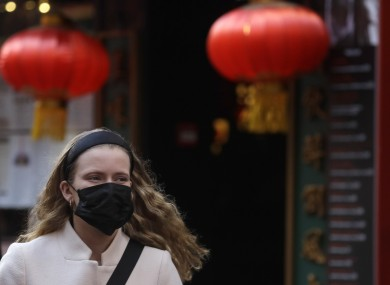 A woman wears a mask as she walks near China Town in London.