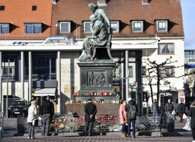Flowers and candles are set around a monument in the market place in Hanau.