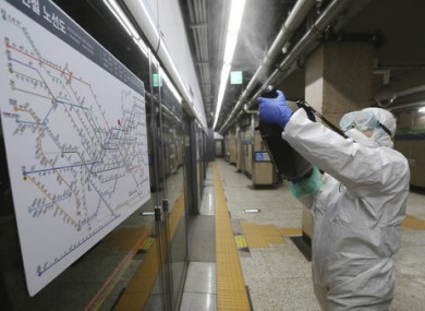 A worker wearing protective gears sprays disinfectant as a precaution against the coronavirus at a subway station in Seoul.