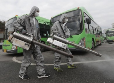 Workers wearing protective suits spray disinfectant in Seoul, South Korea.