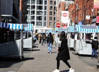 People walk past market stalls on Moore Street, Dublin.