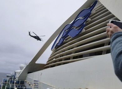 A Coast Guard helicopter delivering virus testing kits hovers above the Grand Princess cruise ship