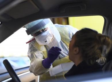 A nurse demonstrates drive-through coronavirus testing procedures.