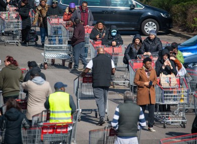Shoppers queue outside a branch of Costco, in Croydon, south London.