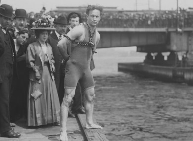 Harry Houdini jumps 30 feet from Harvard Bridge locked up in chains, April 30, 1908. Boston, Massachusetts. His hands were handcuffed and chained to a collar around his neck by a Boston policeman.