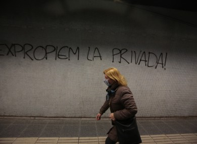 A woman wearing protective mask walks past a graffiti message reading 'Expropriate the private (hospitals and clinics)' inside a train in Barcelona, Spain.