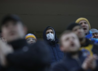 Fans of FC Bate, one of them wearing a face mask, watch on as their team play during the coronavirus pandemic.