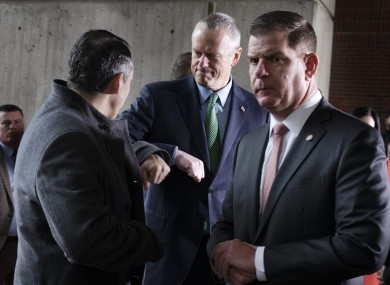 Massachusetts Governer Charlie Baker, centre, bumps elbows with Aaron Michlewitz Mayor Marty Walsh.
