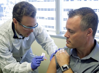 Pharmacist Michael Witte, left, gives Neal Browning an injection in the first-stage safety study clinical trial of a potential vaccine for the COVID-19 coronavirus on Monday at the Kaiser Permanente Washington Health Research Institute in Seattle in the US.
