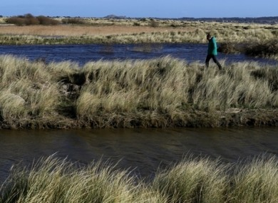 A man walks between flooded areas of Bull Island in Dublin Bay.