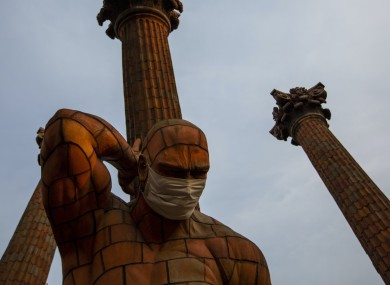 A medical mask covers the face of a statue in Guatemala City.