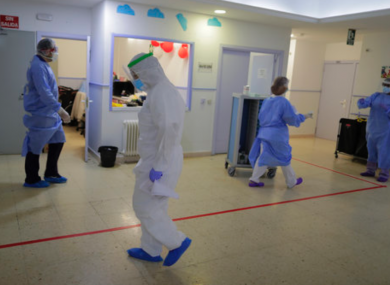 Health workers wear protective suits to protect from coronavirus work at a nursing home in Madrid, Spain.