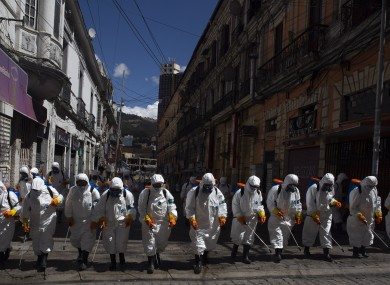 City workers fumigate a street to help contain the spread of the new coronavirus in La Paz, Bolivia.
