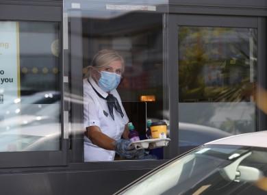 Workers wear face masks while cars pass through the McDonald's drive-thru in Rathfarnham, Dublin.