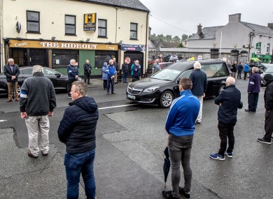 Members of the public and Tullamore GAA adhere to social distancing as the hearse carrying former Offaly footballer and community man Paddy Fenning passes by.