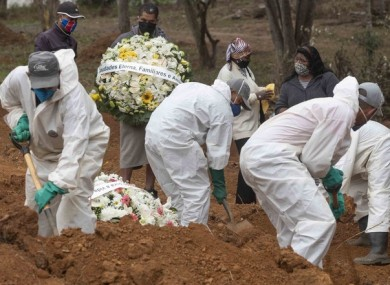 Relatives watch cemetery workers shovel dirt over the coffin of a man who died of Covid-19