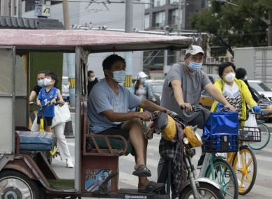 File photo of people wearing face masks in Beijing.