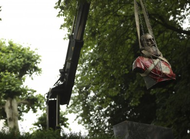 A bust of Belgium's King Leopold II is hoisted off of its plinth by a crane as it's removed from a park in Ghent.