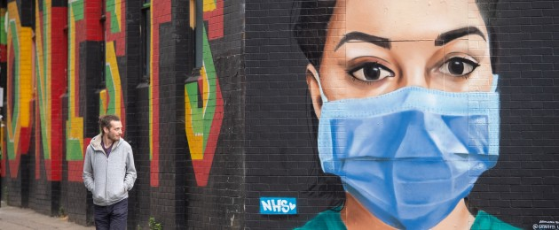 A man looks at a mural showing a worker wearing PPE in London yesterday.