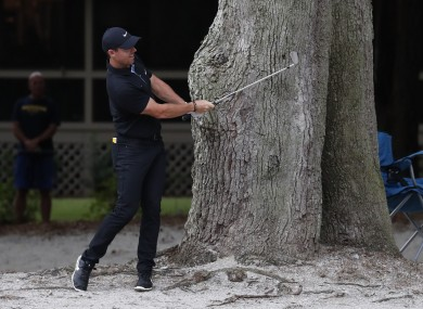 Rory McIlroy hits out of the rough on the 11th hole during the first round.