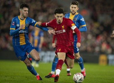 Liverpool's Curtis Jones (R) gets away from Shrewsbury Town's Sean Goss during the English FA Cup 4th Round Replay match.
