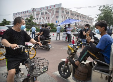 People stop at a checkpoint outside the Xinfadi wholesale food market district in Beijing today.