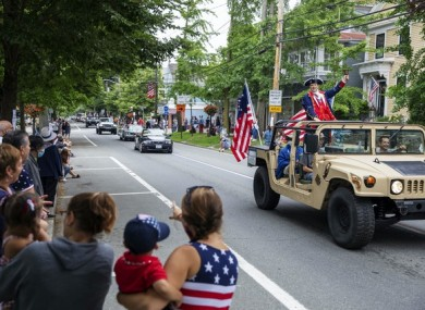 Spectators watch as a Fourth of July parade passes in Bristol, Rhode Island
