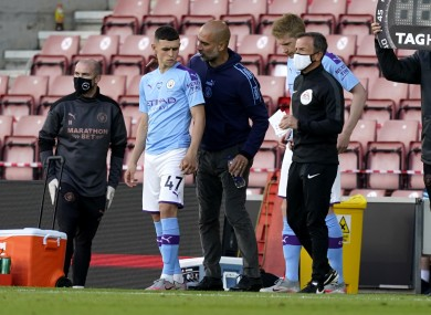 Man City manager Pep Guardiola giving Phil Foden instructions before his introduction.