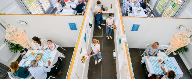 Diners at the UK's only purpose built pop-up socially distanced restaurant, split into separate dining pods with serving hatches under one marquee, the Anti Social Club, in Polzeath, Cornwall