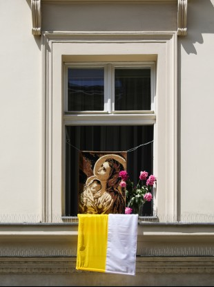 A portrait of Virgin Mary with flowers and a Vatican flag seen on a window during the annual Corpus Christ Procession in  Krakow.