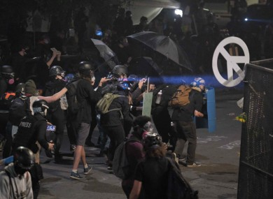 Protesters take cover as federal officers fire crowd control munitions to clear the area after protesters gathered in front of the federal courthouse in Portland