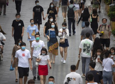 People wearing face masks to protect against the coronavirus walk through an outdoor shopping area in Beijing
