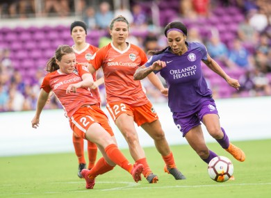 Alli Murphy (21) tackles Sydney Leroux while playing for Houston Dash against Orlando Pride in 2018.
