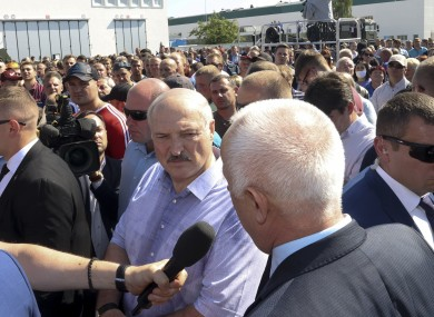 Belarusian President Alexander Lukashenko, center, surrounded by his bodyguards listens to an employee of the Minsk Wheel Tractor Plant