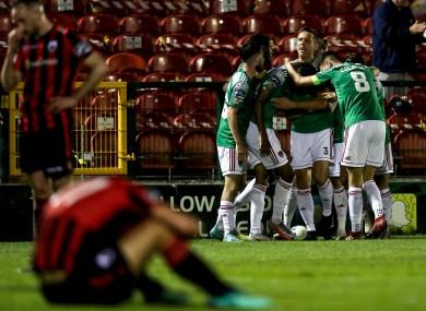 Longford slump in dejection as Cork celebrate their winning goal.