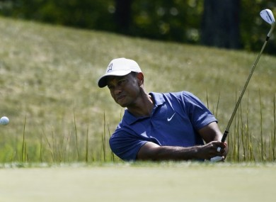 Tiger Woods makes his first attempted shot out of a trap on the fourteenth tee during the third round of the Northern Trust golf tournament.