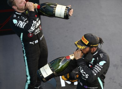 Race winner, Mercedes driver Lewis Hamilton of Britain, front, drinks champagne with third placed Mercedes driver Valtteri Bottas of Finland.