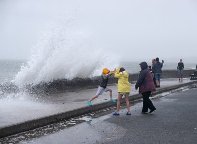 People are hit by waves on the Front Strand in Youghal, Co. Cork on 19 August ahead of Storm Ellen.