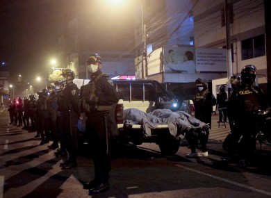 Police officers stand guard near two bodies outside of a disco in Lima, Peru