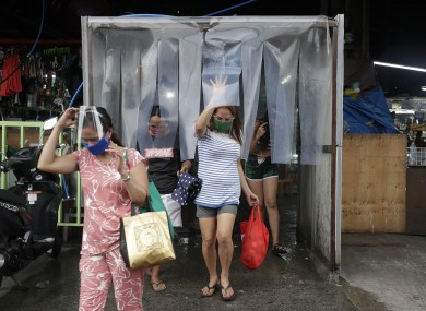 Women exit from a disinfecting area after buying food at a public market in Quezon City in the Philippines.
