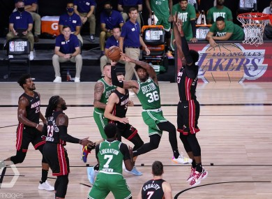 Boston Celtics guard Marcus Smart (36) passes the ball out as Miami Heat's Bam Adebayo, right, blocks the path to the net.