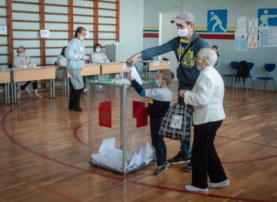 A young child helps his father place his vote in a ballot box at a polling station in Russia.