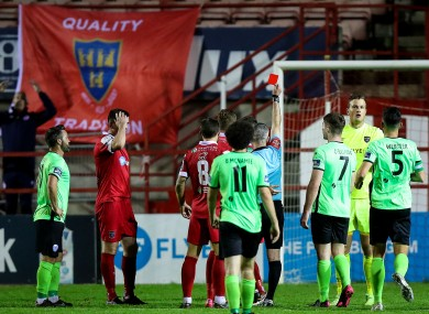 Players look on as Luke Byrne is given a red card.