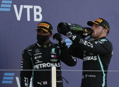 Race winner, Mercedes driver Valtteri Bottas of Finland, right, drinks champagne with third placed Mercedes driver Lewis Hamilton of Britain after the Russian Formula One Grand Prix.