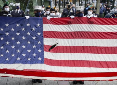 A giant American flag is unfurled as the national anthem is plated at the National September 11 Memorial and Museum.