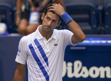 Novak Djokovic, of Serbia, reacts after inadvertently hitting a line judge with a ball.