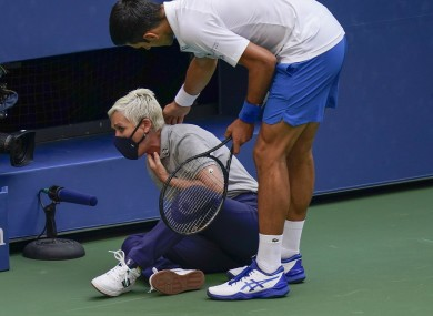 Novak Djokovic, of Serbia, checks a female official after hitting her with a ball.