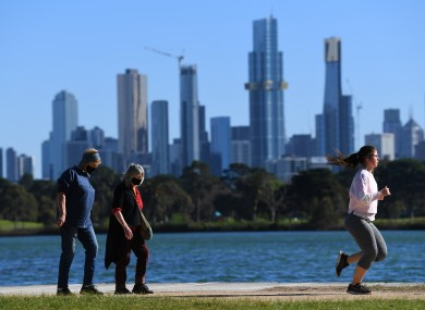 People are seen exercising along Albert Park Lake in Melbourne